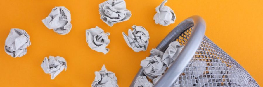 Grey crumpled paper balls rolling out of a trash can