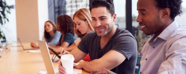 Businessmen And Businesswomen Working In Shared Open Plan Office Workspace