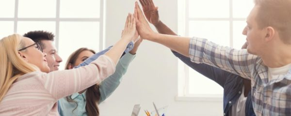 Successful young business team is giving high five